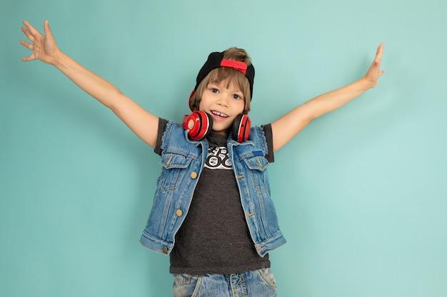 Heureux Garçon Adolescent En Short Et Veste En Jean, T-shirt Noir, Casquette Noire, Avec Des Sourires Rouges Et Sourit Photo Premium