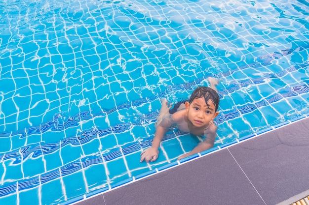 Heureux garçon assis autour de la piscine et à la recherche Photo Premium
