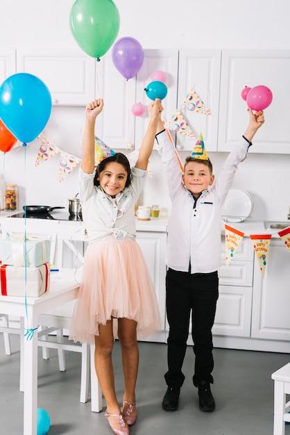 Heureux garçon et fille debout dans la cuisine tenant des ballons colorés à la main Photo gratuit