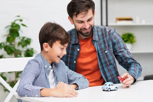 Heureux garçon jouant avec de petites voitures avec son père Photo gratuit