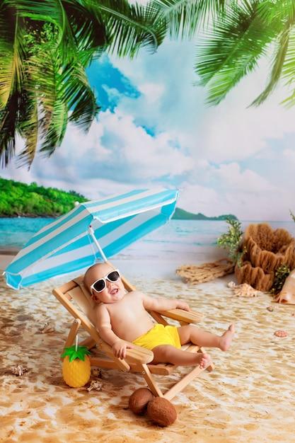 Heureux Garçon à Lunettes Se Trouve Sur Une Chaise Longue, Des Bains De Soleil Sur Une Plage De Sable Avec Des Palmiers Au Bord De La Mer Photo Premium