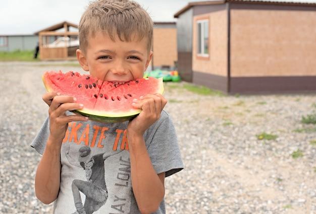 Heureux garçon mange une pastèque mûre. Photo Premium
