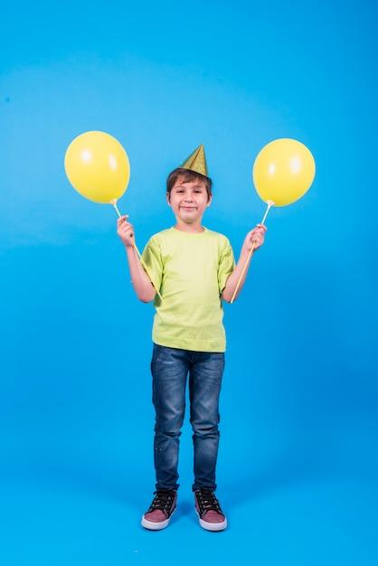 Heureux garçon portant chapeau de fête tenant des ballons en fond bleu Photo gratuit