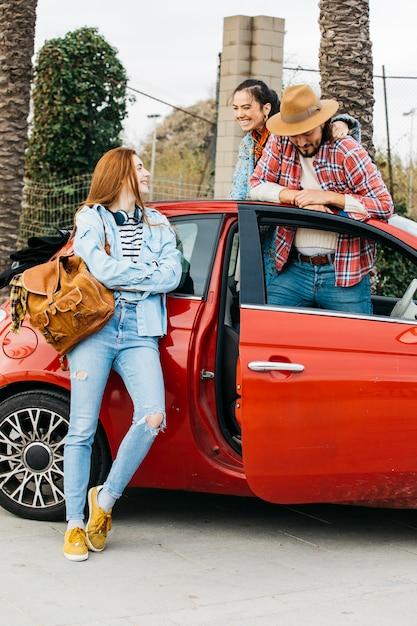 Heureux gens debout près de voiture rouge Photo gratuit
