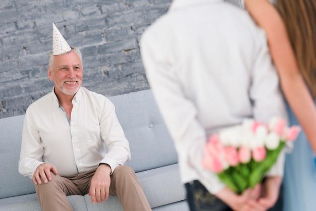 Heureux grand-père regardant ses petits-enfants cachant des cadeaux derrière leur dos Photo gratuit