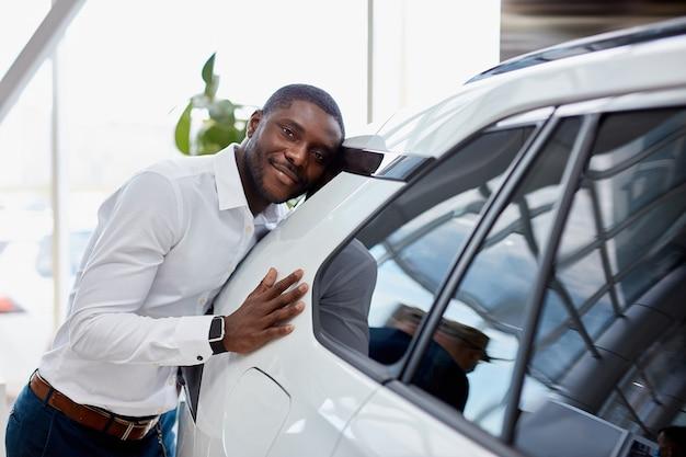 Heureux Homme D'affaires Africain Embrasse Sa Nouvelle Voiture De Luxe Blanche Chez Le Concessionnaire Photo Premium
