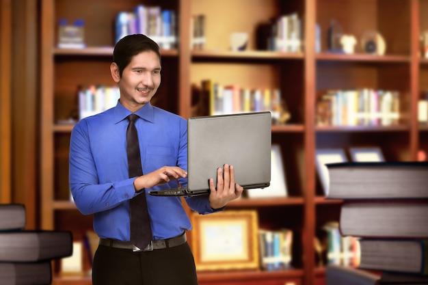 Heureux homme d'affaires asiatique travaillant avec un ordinateur portable Photo Premium