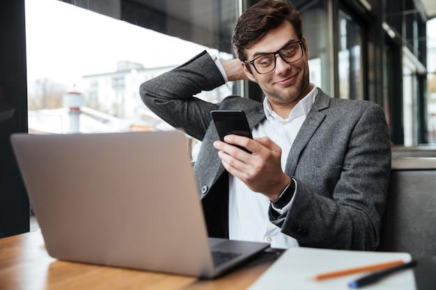 Heureux Homme D'affaires à Lunettes Assis Près De La Table Au Café Avec Un Ordinateur Portable Tout En Utilisant Un Smartphone Photo gratuit