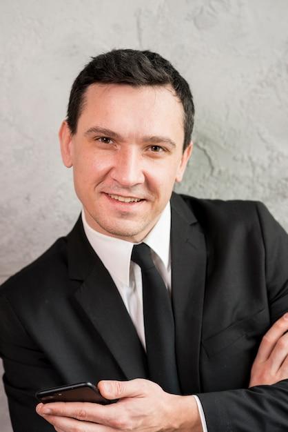 Heureux homme d'affaires avec smartphone souriant à la caméra Photo gratuit