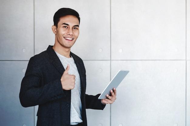 Heureux homme d'affaires souriant et montrer les pouces en utilisant une tablette numérique Photo Premium