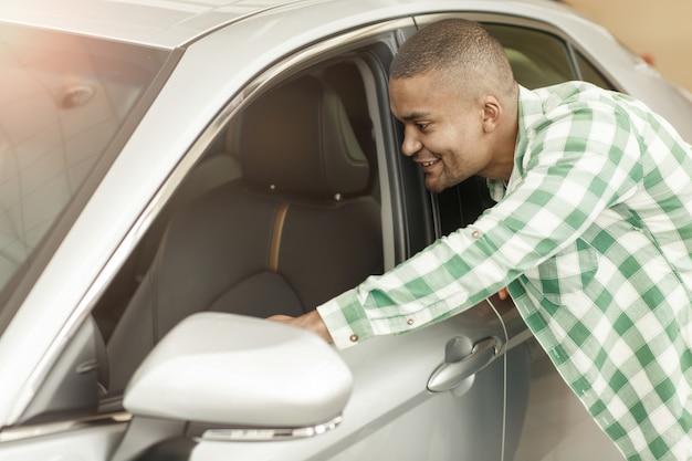 Heureux Homme Africain Cherche à L'intérieur D'une Nouvelle Voiture Chez Le Concessionnaire. Photo Premium