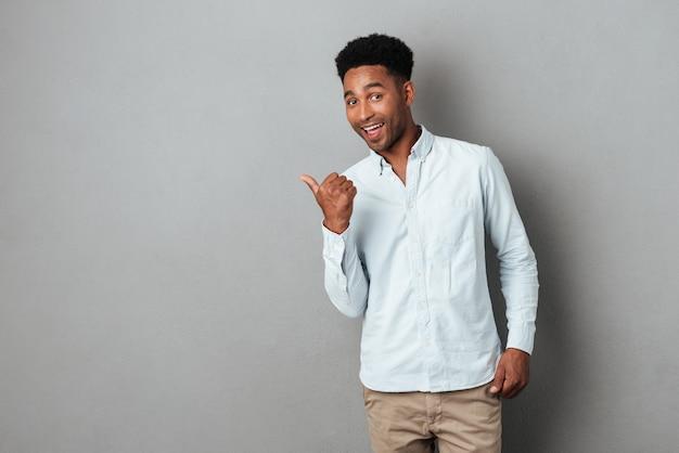 Heureux Homme Africain Excité, Pointant Le Doigt Vers L'espace De Copie Photo gratuit