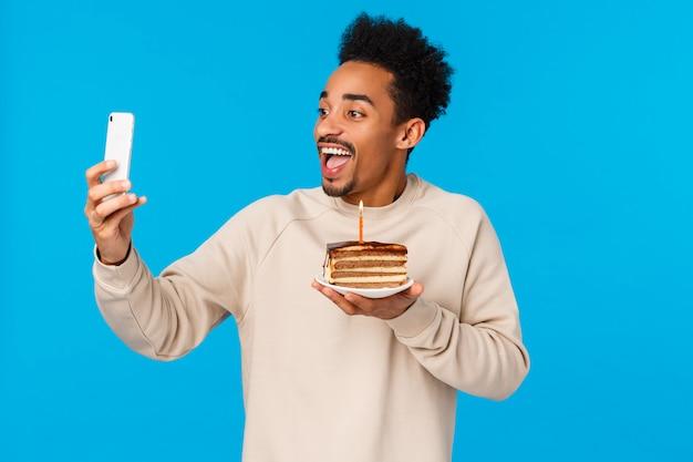 Heureux Homme Afro-américain Barbu Hipster Barbu Tenant Un Morceau De Gâteau Avec Une Bougie D'anniversaire, Souriant Joyeusement En Prenant Un Selfie Ou Enregistrer Une Vidéo Comment Il Célèbre, En Souhaitant, Debout Mur Bleu Photo Premium