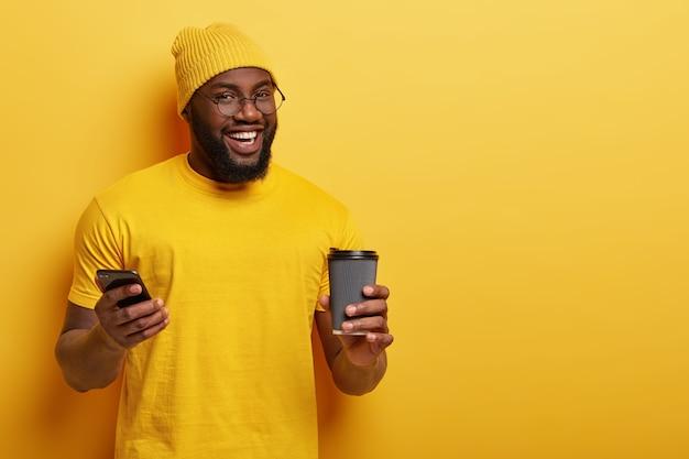 Heureux Homme Afro-américain Lit Le Fil De Nouvelles Dans Les Réseaux Sociaux, Profite D'une Boisson Chaude Dans Un Gobelet Jetable Photo gratuit