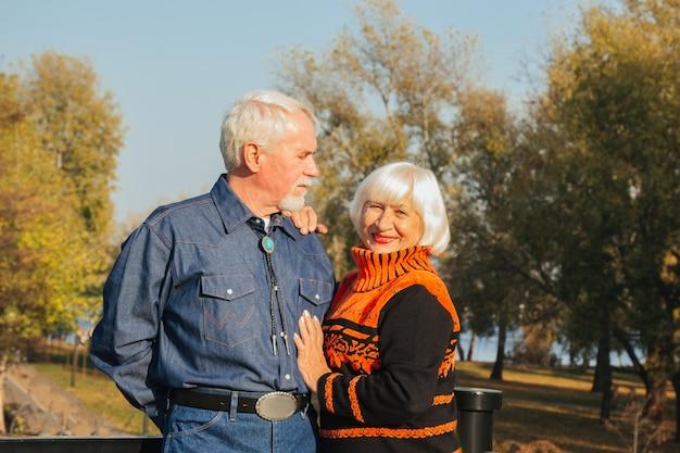 Heureux Homme âgé Et Femme Assise Sur Un Banc En Journée D'automne. Photo Premium
