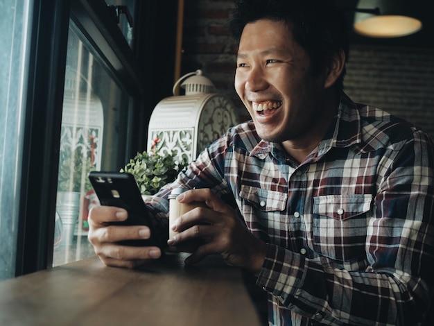 Heureux homme asiatique boire du café et utiliser un téléphone intelligent dans le café-restaurant. Photo Premium