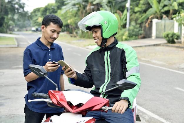 Heureux homme asiatique commande moto taxi par téléphone mobile Photo Premium