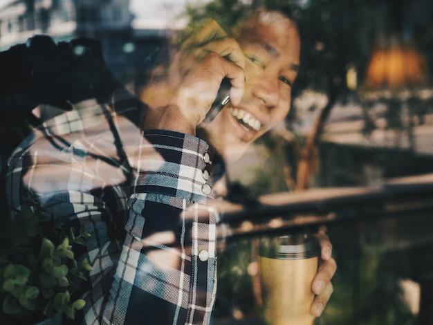 Heureux homme asiatique parler au téléphone dans le café-restaurant. Photo Premium