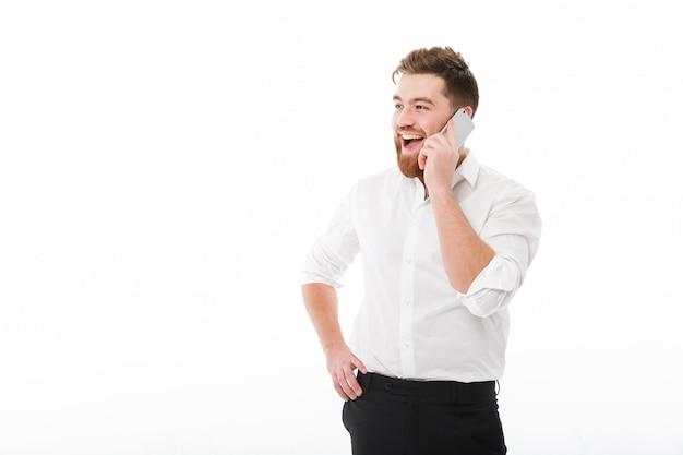 Heureux Homme Barbu Dans Des Vêtements D'affaires Parlant Par Smartphone Photo gratuit