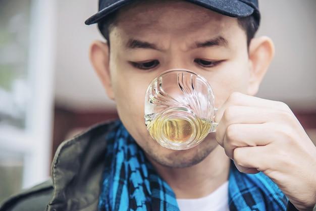 Heureux homme boire une tasse de thé chaud - les asiatiques avec une boisson au thé chaud se détendre concept Photo gratuit