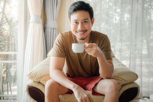 Heureux homme boit du café et se détendre à la lumière du matin. Photo Premium