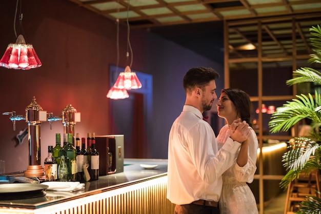 Heureux homme dansant avec une femme joyeuse près de comptoir Photo gratuit