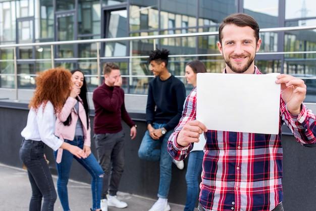 Heureux homme debout avec ses amis tenant une carte vierge dans ses mains Photo gratuit