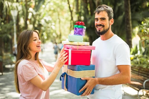Heureux homme donnant une pile de cadeaux à sa petite amie Photo gratuit
