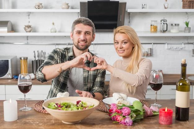 Heureux homme et femme montrant le cœur des mains et assis à table dans la cuisine Photo gratuit