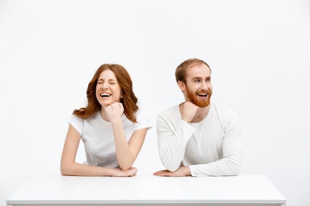 Heureux Homme Et Femme Rousse Riant à Table Photo gratuit