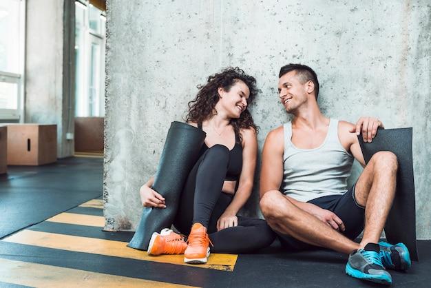 Heureux homme et femme avec tapis d'exercice assis dans une salle de sport Photo gratuit