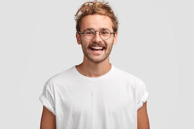Heureux Homme Hipster Avec Un Sourire à Pleines Dents, Porte Un T-shirt Blanc Décontracté Et Des Lunettes Photo gratuit