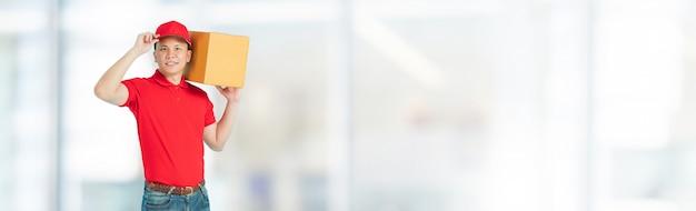 Heureux Homme De Livraison Asiatique Portant Une Chemise Rouge Portant Des Boîtes De Colis En Papier Photo Premium