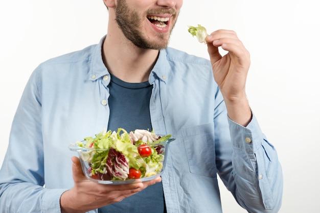 Heureux homme mangeant une salade saine sur fond blanc Photo gratuit