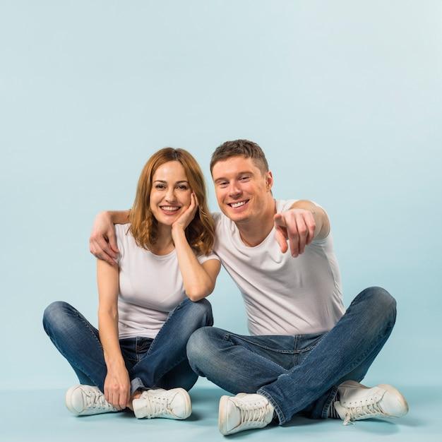 Heureux homme montrant à sa copine quelque chose avec son doigt pointé vers la caméra Photo gratuit