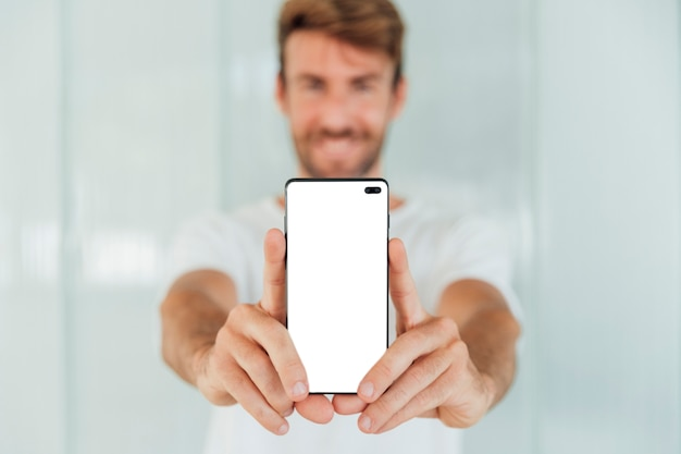 Heureux homme montrant un smartphone avec maquette Photo gratuit