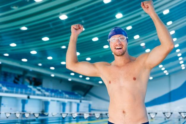 Heureux homme nageur qui lève les mains Photo gratuit