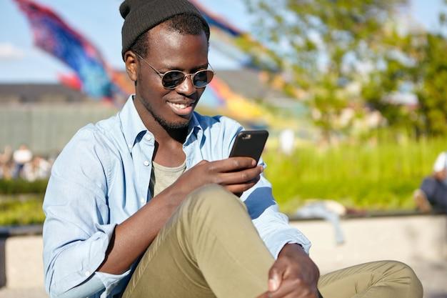 Heureux Homme à La Peau Foncée, Portant Des Lunettes De Soleil Et Des Vêtements à La Mode, Lisant Des Sms Agréables Sur Un Téléphone Portable, Tapant Une Réponse. Homme Souriant à La Peau Sombre à L'aide D'un Téléphone Intelligent à L'extérieur, Toujours En Contact Photo gratuit
