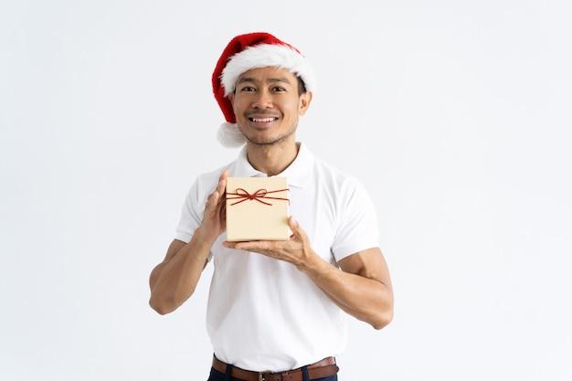 Heureux homme portant bonnet et montrant une boîte cadeau Photo gratuit