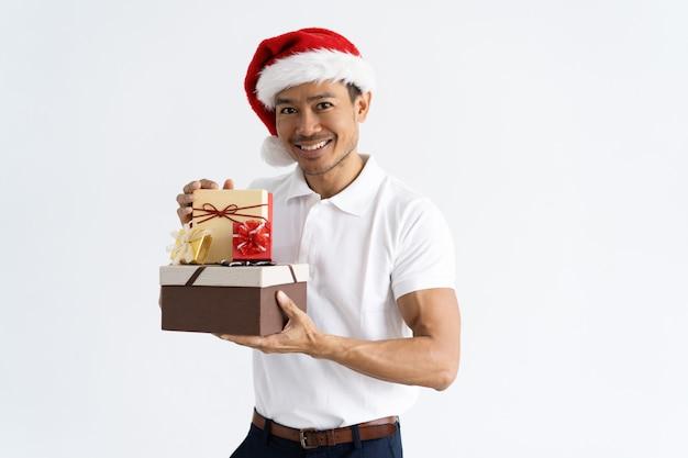 Heureux homme portant bonnet et montrant des boîtes-cadeaux Photo gratuit