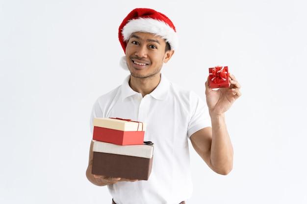 Heureux homme portant bonnet de noel et montrant des coffrets cadeaux petits et grands Photo gratuit