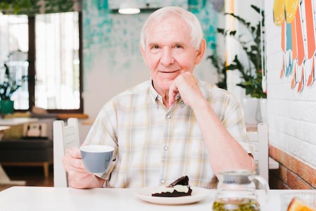 Heureux homme senior assis dans un café en appréciant thé et dessert Photo gratuit
