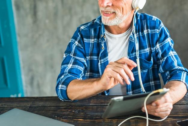 Heureux homme senior écoute de la musique à travers le casque sur tablette numérique Photo gratuit