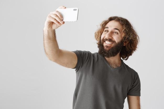 Heureux Homme Souriant Du Moyen-orient Prenant Selfie Avec Smartphone Photo gratuit