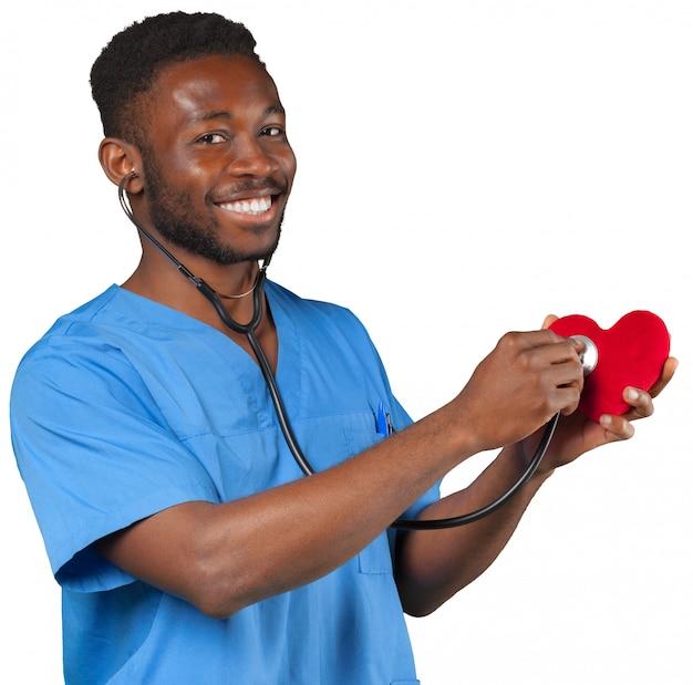Heureux homme souriant médecin avec stéthoscope tenant coeur Photo Premium
