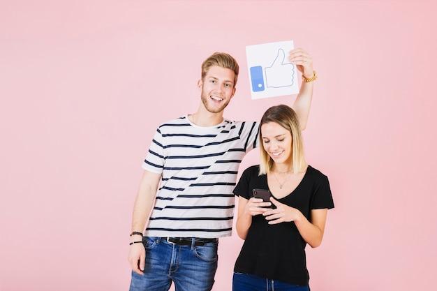 Heureux homme tenant les pouces vers le haut de geste sur la femme à l'aide de téléphone portable Photo gratuit