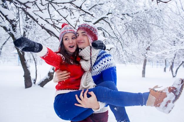 Heureux homme tient sa petite amie dans ses bras en forêt d'hiver Photo Premium