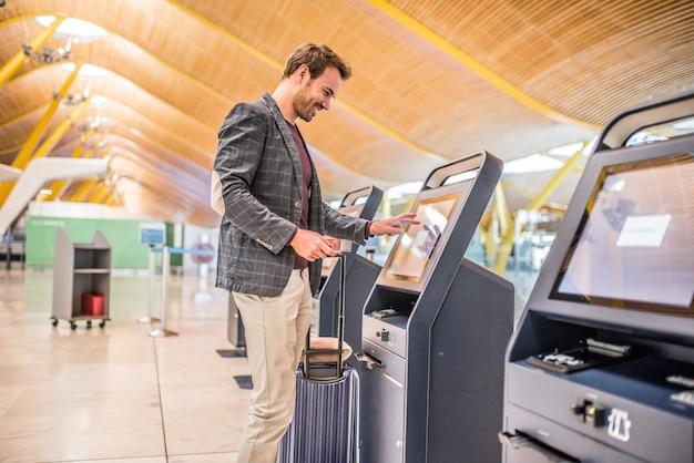 Heureux Homme Utilisant La Borne D'enregistrement à L'aéroport Pour Obtenir La Carte D'embarquement. Photo Premium