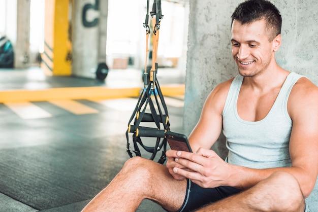 Heureux homme utilisant un téléphone portable dans une salle de sport Photo gratuit