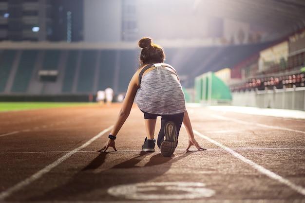Heureux jeune athlète féminine à une position de départ dans le stade Photo Premium